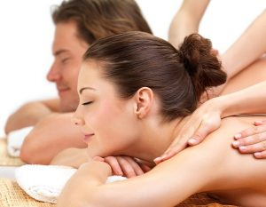 Young beautiful happy woman getting a massage at the spa with her boyfriend