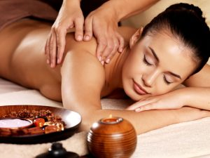 Masseur doing massage on woman body in the spa salon. Beauty treatment concept.